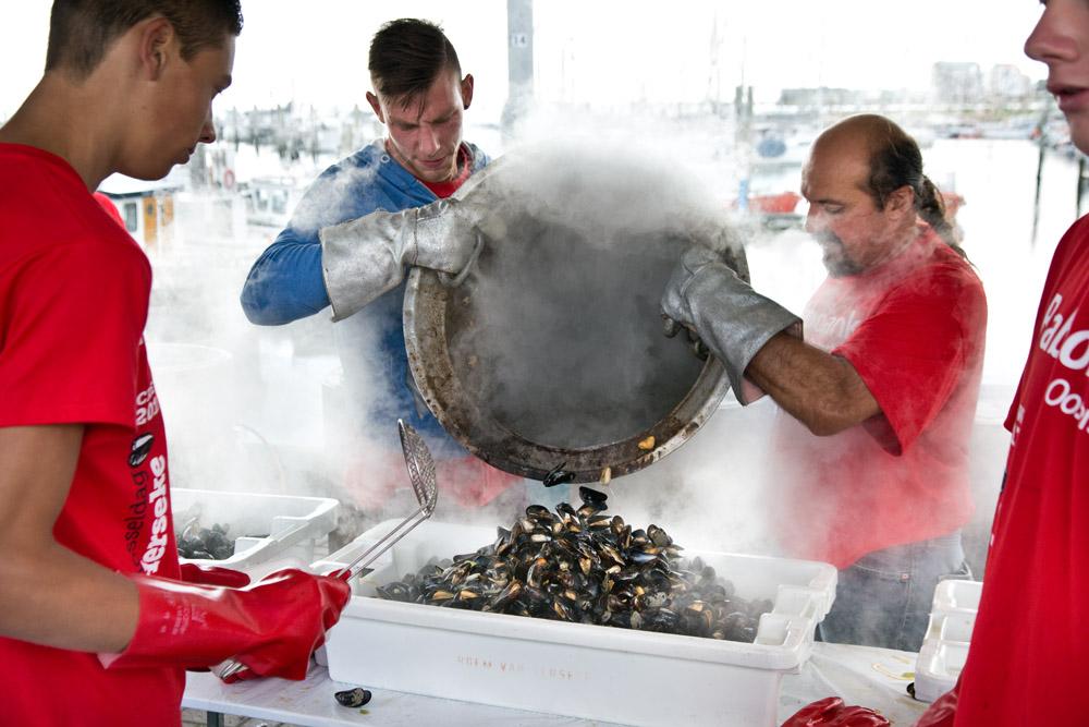 Mannen storten gekookte mosselen in een bak om te verkopen tijdens de mosseldag in Yerseke. De hete stoom komt uit de pan.