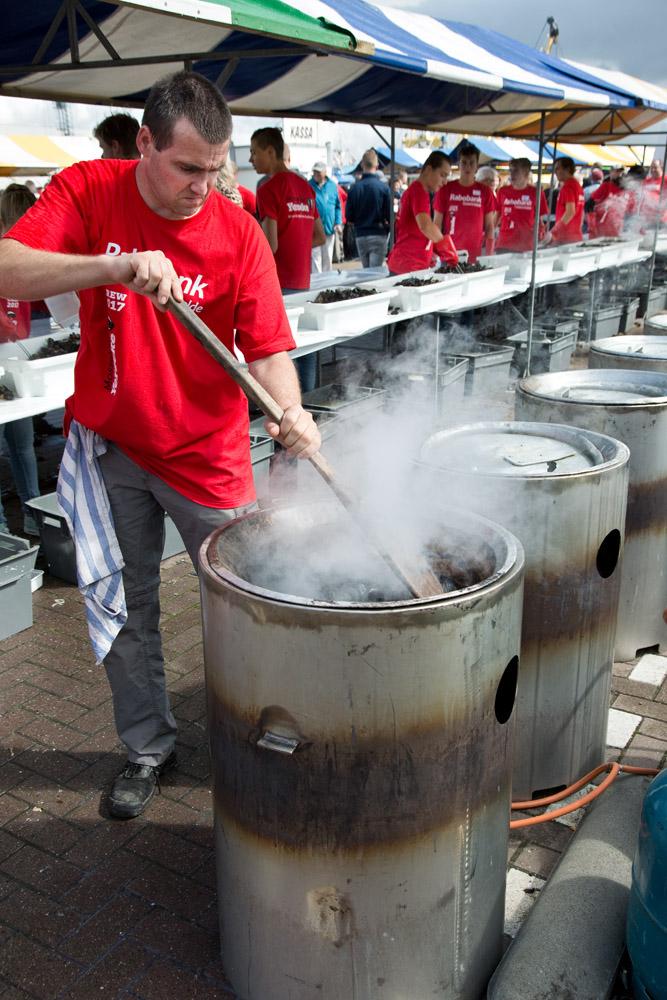 De kok tilt het deksel op van de ketel om te kijken of de mosselen al gaar zijn, tijdens de mosseldag in Yerseke. Dit is een jaarlijks terugkerend evenement.